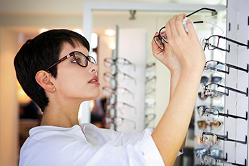 woman selecting a pair of glasses